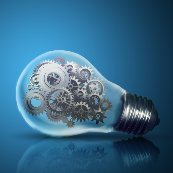 Close up of light bulb with gear mechanism inside isolated on dark blue background-crop