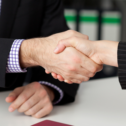 Businessman and businesswoman shaking hands at office desk_crop